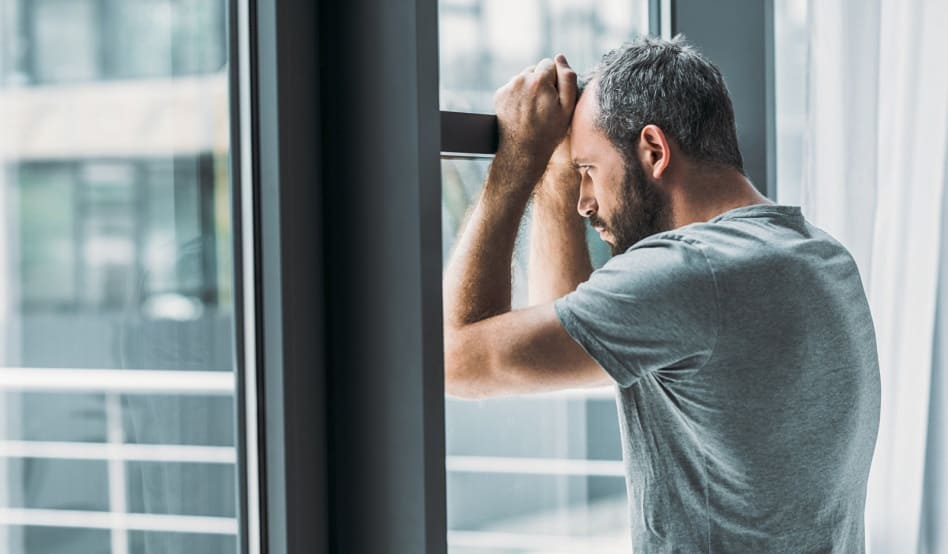 Deprimierter bärtiger Mann, der sich ans Fenster lehnt und durch Fenster draußen schaut.