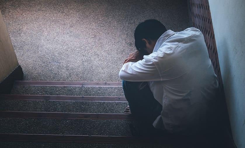 Deprimierter Mann sitzt auf der Treppe