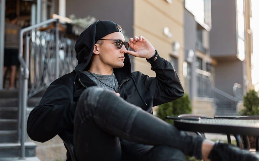 junger und stylischer Mann mit Cap und Sonnenbrille