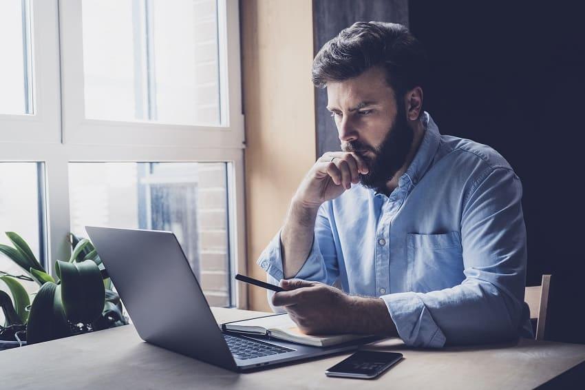 Mann sitzt vor seinem Laptop mit Handy in der Hand