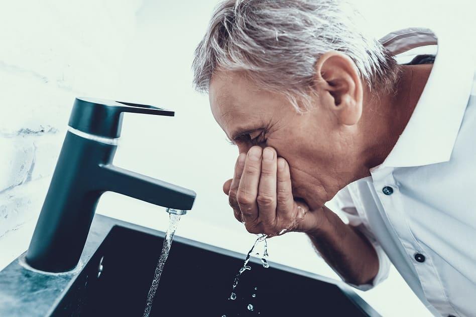 Alter Mann trinkt Wasser