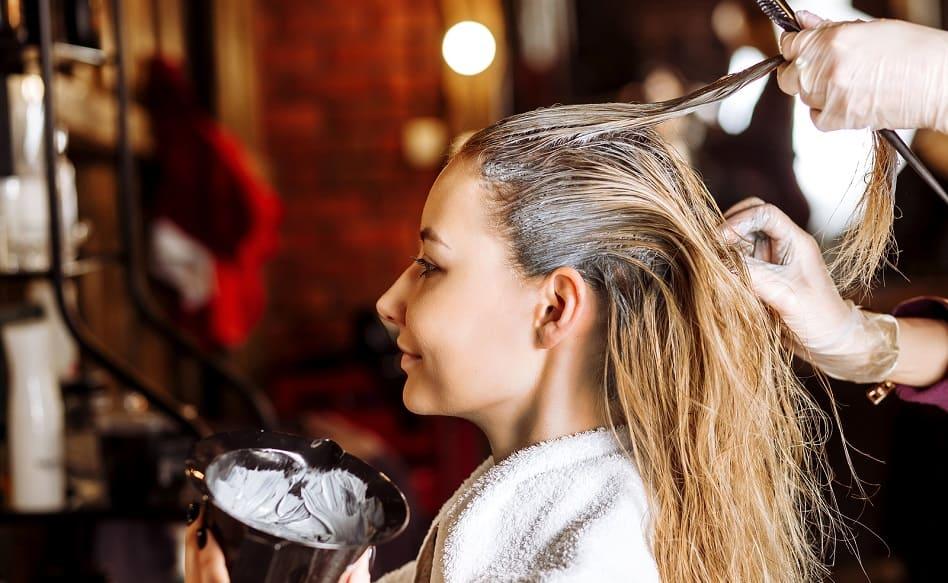 Blonde Frau laesst sich die Haare faerben