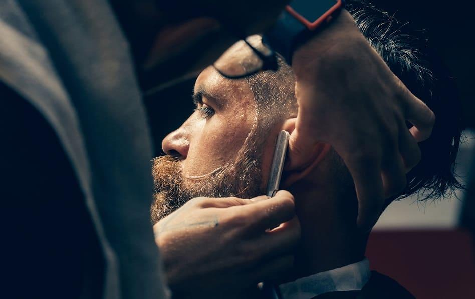 Ein Mann erhaelt beim Barbier eine frische Bartform