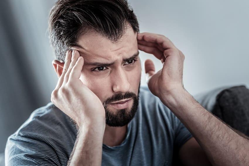 Mann hat Geheimratsecken und Migraene wegen Stress