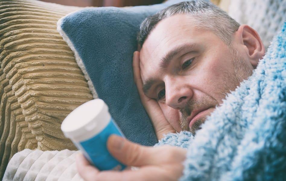 Mann liegt und schaut sein Medikament an