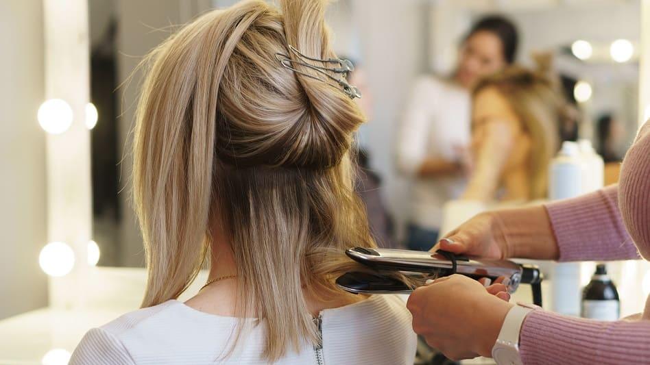 Blonde Frau beim Haare glätten mit Zopf