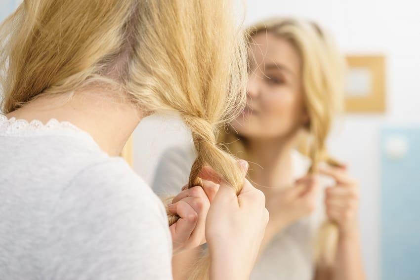 Blonde Frau flechtet die Haare