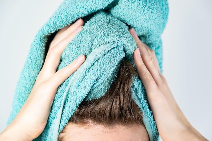 Eine Frau trocknet sich die Haare mit einem Handtuch