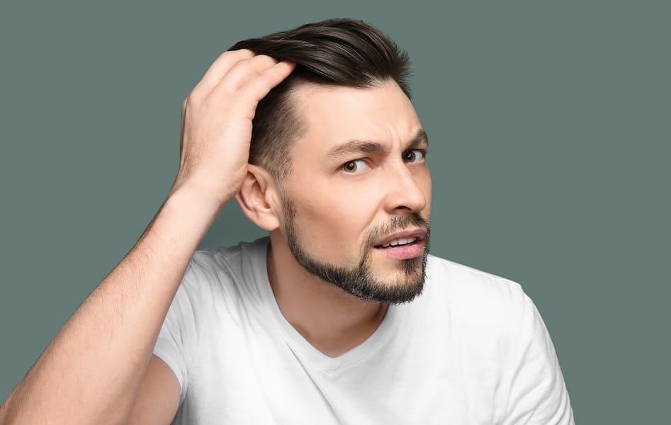 Mann fässt sich durch die dünnen Haare