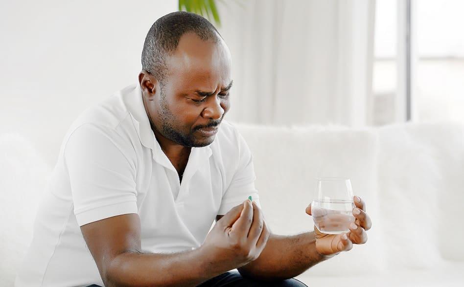 Mann nimmt Tablette ein