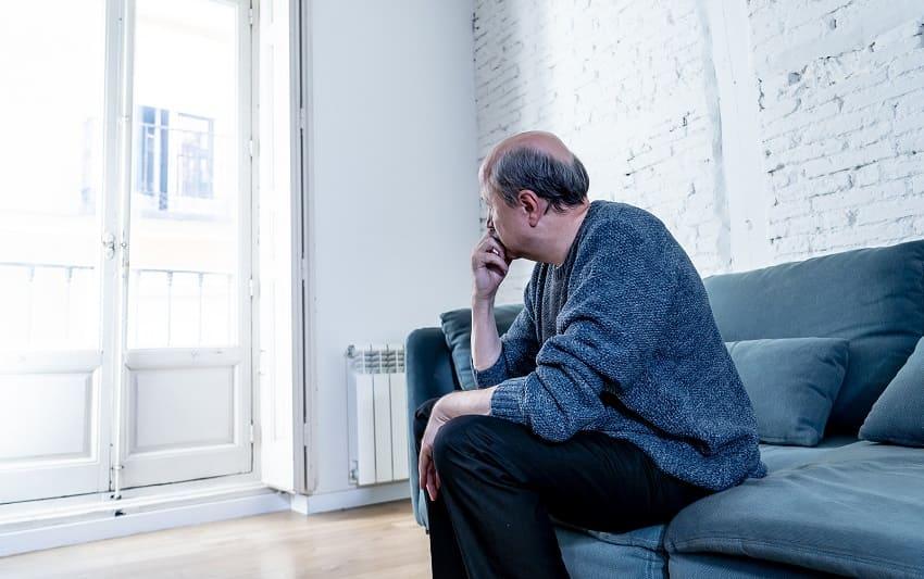 Mann mit Haarkranz schaut nachdenklich aus dem Fenster