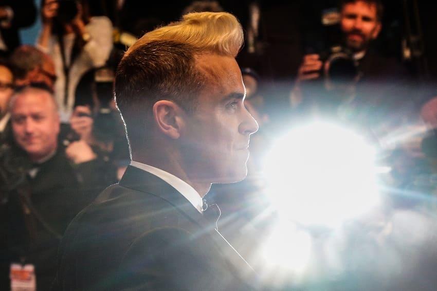 Robbie Williams von der Seite in einem Scheinwerferlicht