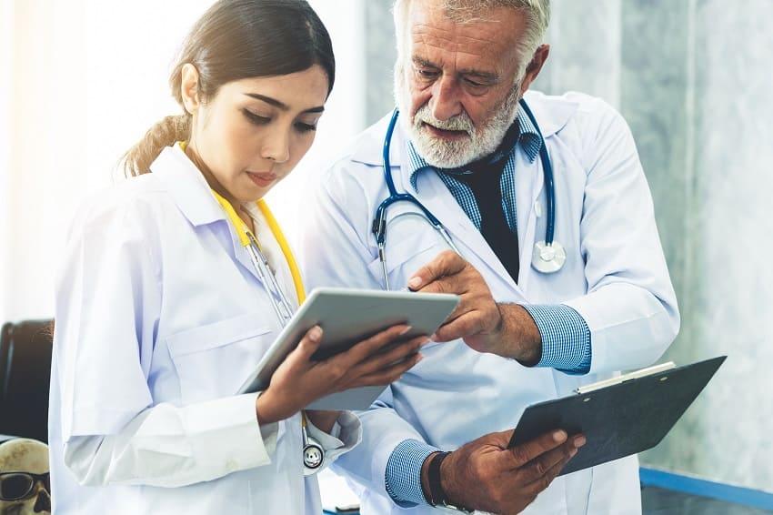Zwei Experten haben ein Tablet in der Hand und beraten sich
