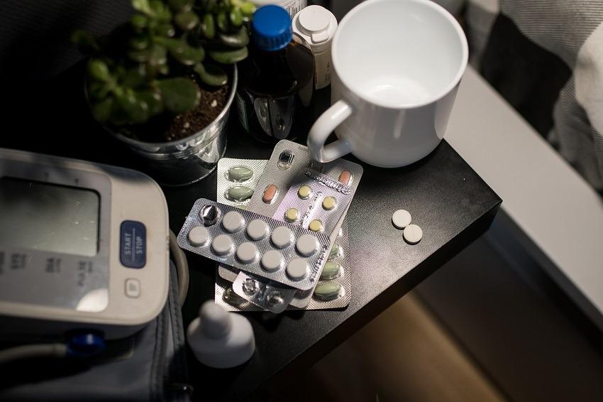 auf einem Nachttisch liegen Tabletten und ein Blutdruckmessgerät