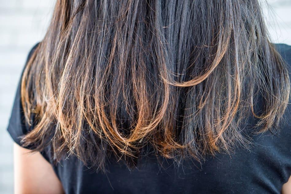 Frau mit hellen Haarspitzen hat trockene Haare