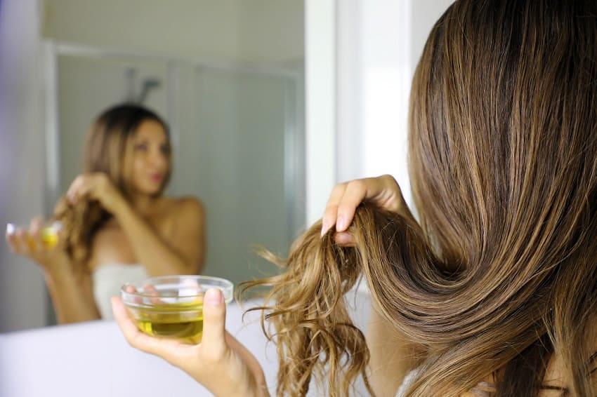 Junge Frau oelt sich die Haare nach dem Duschen
