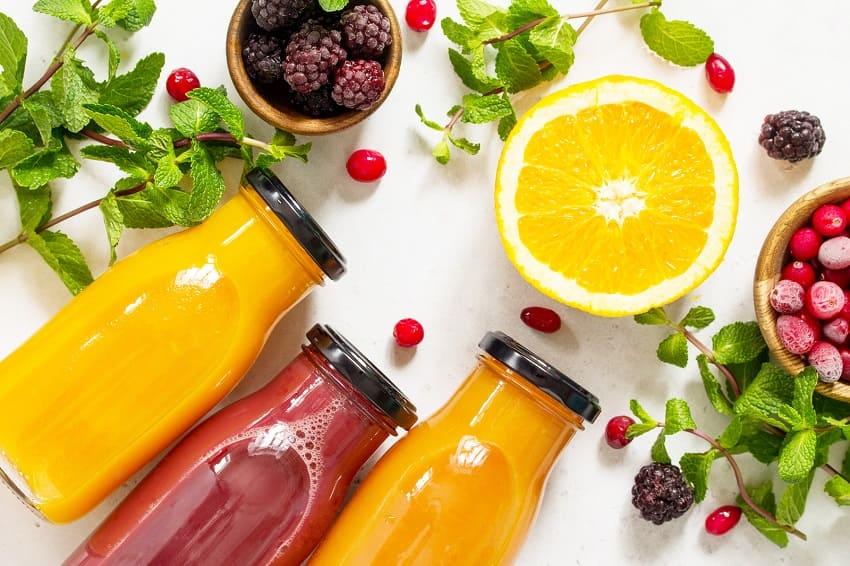 3 Smoothies und Obst auf einem Tisch als Vitamin C Lieferanten