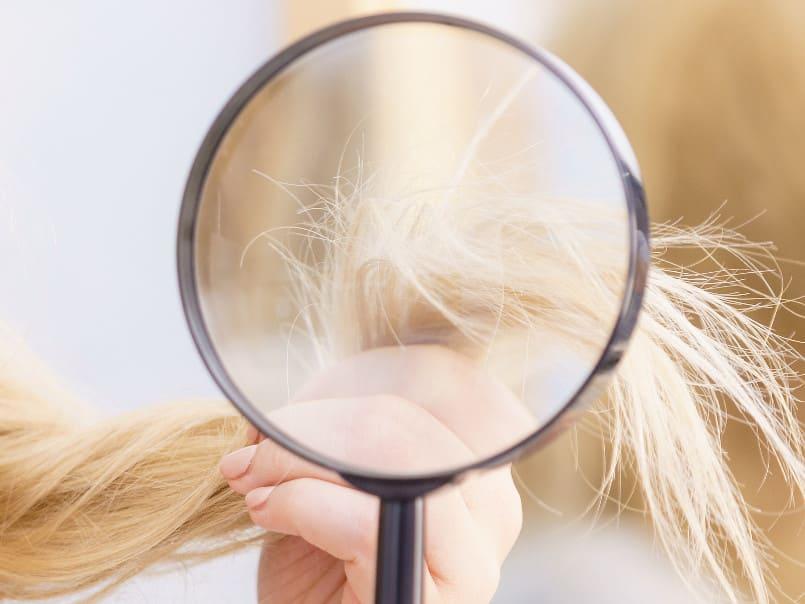 Eine Frau untersucht den Spliss ihrer Haare mit einer Lupe