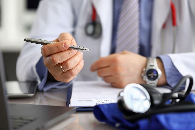 Arzt hält, während eines Beratungsgesprächs, einen Stift in der Hand
